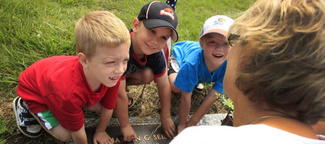 Eudora residents, from left, Simeon Chrislip, 5, Joel Jubber, 3, and Caleb Chrislip, 5, touch the grave of their great-grandfather in Memorial Park Cemetery as Diane Chrislip talks about his legacy on Memorial Day.