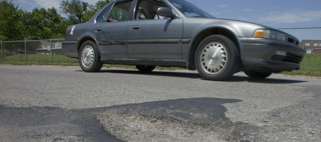 A motorist dodges a pothole Friday on Connecticut Street near 15th Street. After a long, hard winter, city officials and motorists are seeing a lot of them and figuring out how to fill them or avoid hitting them.
