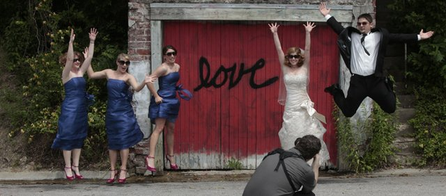 Members of A wedding party were having a few wedding pictures taken Sunday along Mississippi Street. Bridesmaids, from left, Katie Geier, Erica Schmidt and Danyel Deitrich catch some air along with newly married couple Abby and Tully Corcoran, both of Lawrence, as photographer Aaron Newell captures the moment.