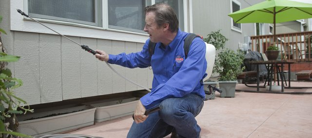 Pete Haley, of Haley Pest Control, sprays for ants at a Lawrence home on Wednesday. Local pest control businesses have seen an increase in ant extermination requests in the past several weeks.