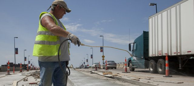 Bob Lassen, an employee with Sunflower Concrete, Lawrence, applies cement-curing spray to a new median strip on North Second Street on the north side of the Kansas River Bridge on Friday. The work being done at the intersection of North Second and Elm streets is one of several area projects funded by the American Recovery and Reinvestment Act — the federal stimulus program.
