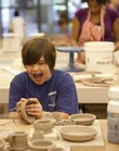 Jacob Russell, 12, breaks into laughter as he talks with other students in the ceramics studio Wednesday at the Lawrence Arts Center. The center is celebrating its 35th anniversary this year with several events that will look back on its history.