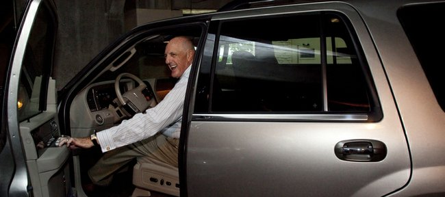 Kansas University athletic director Lew Perkins smiles as he is approached by media members Thursday in the parking garage adjacent to Allen Fieldhouse. On Thursday, Perkins announced his intention to resign from his position after the 2010-11 academic year but did not comment.