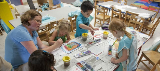 Kansas University Graduate student Katie Pierson, left, works with preschoolers on painting during the first day of summer classes Wednesday at the Dole Center. KU's Language Acquisition Preschool is marking 25 years of service.