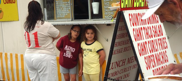 Samantha Angell, 9, and her sister, Sydney Angell, 7, try to stay dry by squeezing under the counter of a vending stand as a light rain falls Saturday in downtown Tonganoxie. Heavy rains that started about 9 a.m. Saturday drastically reduced attendance at the annual Tonganoxie Days event and made many vendors head home before the sun made an appearance during the mid-afternoon.