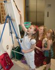 Bailey Landholm, 6, Lawrence, left, adds her artistic stylings to a painting at the Lawrence Arts Center on Saturday during the centers Street PArty. At center is Lori Hanson, the LACs childrens painting and drawing instructor, and at right is Baileys sister Lindsey, 4.