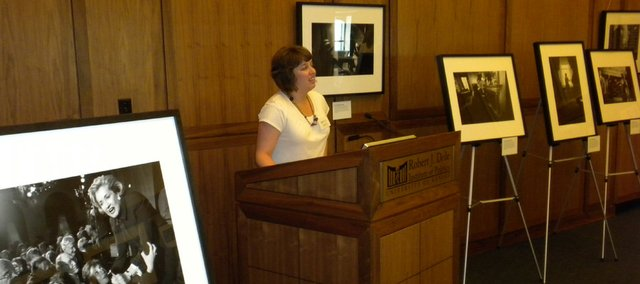 Dole Institute of Politics Senior Archivist Morgan Davis opens the institute's exhibit by photojournalist Melina Mara. The far left photo captures U.S. Sen. Elizabeth Dole, R-N.C., almost being pulled off a stage by well-wishers. Mara took the photos in 2001-2003. She is now a photographer for the Washington Post.