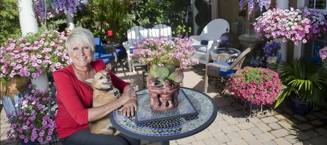 Judy LaFond makes the most of limited garden space with several containers overflowing with plants. LaFond sits with her dog Scrappy, on her backyard patio.