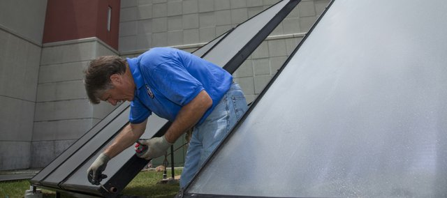 Jeff Morrow, owner of Solar Heat Exchange Manufacturing, works on installing solar panels Tuesday outside the Douglas County Jail. The panels will be used to heat water at the jail.