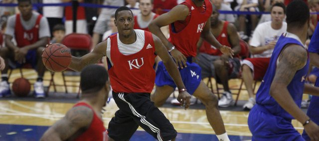 Red team guard Mario Chalmers pushes the ball up court to Keith Langford during the alumni scrimmage Wednesday, June 16, 2010 at the Horejsi Center.