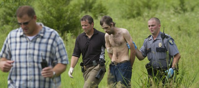 Lawrence police officers and Douglas County sheriff deputies detain a suspect in a stabbing incident along the bike path near Clinton Lake. William E. Nichols was arrested after a 15-minute manhunt in the area between the YSI softball fields and the Clinton Lake Dam Wednesday, June 16, 2010.