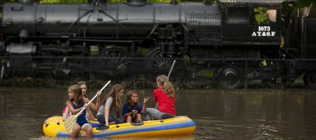 A group of friends (clockwise from front left), Chloe Riedemann, 13; Krista Griffin, 11; Nora Birchfield, 11; Sophi Riedemann, 10; and Maddie Birchfield, 13, paddle past the train at Buford M. Watson Park after the rain had stopped and the flood water had somewhat receded Wednesday.