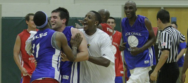 Stephen Vinson, center, is mobbed by Aaron Miles (11) and Mario Chalmers after Vinson scored the winning basket in the final second of the Rock Chalk Roundball Classic. Former Jayhawks participated in the game Thursday night at Free State High.