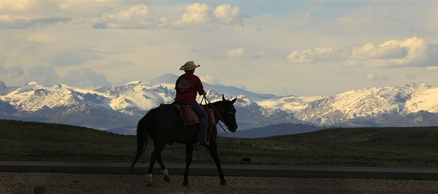 With snow on the Wind River Mountains along side them, Cindy Watkins, 27, and her horse Socks head east along Wyoming Highway 28, on June 15, the ninth day of the 150th anniversary commemorative ride of the Pony Express.
