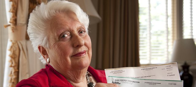 Lawrence resident Barbara Bishop is pictured Friday with two fraudulent checks written to her husband, Kenneth Bishop. Bishop received both checks, which are written for amounts exceeding $3,600, accompanied by two fraudulent sweepstakes letters by mail. Bishop would like others to be aware of the scam.