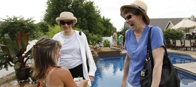 Lawrence residents Carolyn Beasley, right, and Ursula Stammler laugh as they talk shop with homeowner Bobbi Strayer about her garden Saturday during a stop on the Tour Des Fleurs in the Briarwood subdivision. Strayer was one of several Lawrence residents to open her home to the viewing public for the tour.
