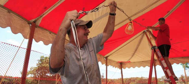 Rod Karlin, left, of Lawrence, and Al Cappel, of Leavenworth, hang lights in preparation for the opening of the Midwest Fireworks stand at 31st Street and Kasold Drive in this June 2010 file photo.