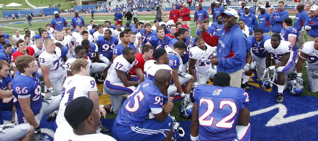 Kansas University football coach Turner Gill, right, addresses his team following the spring game on April 24 at Memorial Stadium. Gill has implemented a cell-phone policy on the team, as cell phones are collected on the d