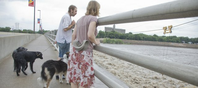 Patrick McCaffery and Lorelei Jordan, both of Lawrence, watch the high and fast current of the Kansas River during a walk with their dogs Monday across the bridge. Recent rain could cause the Kansas River in Lawrence to rise to near-flood levels by this evening.