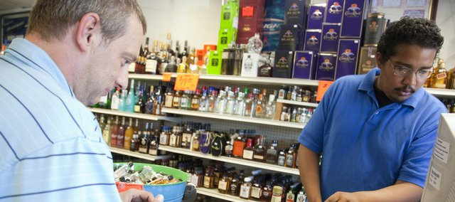 Cashier Noah Wallace rings up the purchase of William Brown, of Lawrence, on Friday at Myers Retail Liquor, 902 W. 23rd St.