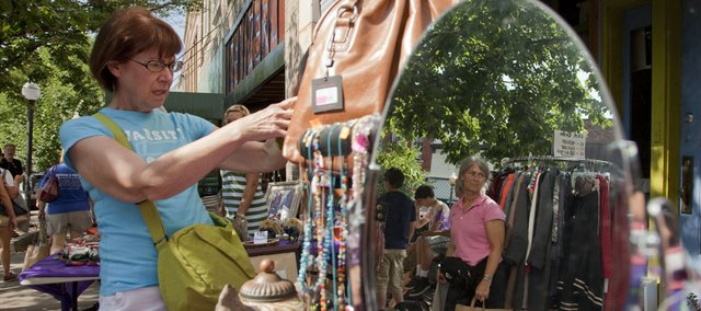 Jane Fowler, Topeka, left, looks over purses at Prairie Pond Studio and Bead Co. while another shopper is reflected in a mirror nearby during the 2009 Downtown Lawrence Sidewalk Sale. This year's event is Thursday.