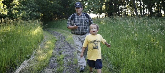 Jay Kennedy, left, and his son, Nick Kennedy, 6, hike out of the woods in Clinton Lake State Park during a geocaching adventure in this file photo from June 2008. Geocachers use GPS to search, with provided coordinates, for a hidden object - sort of a high-tech scavenger hunt.