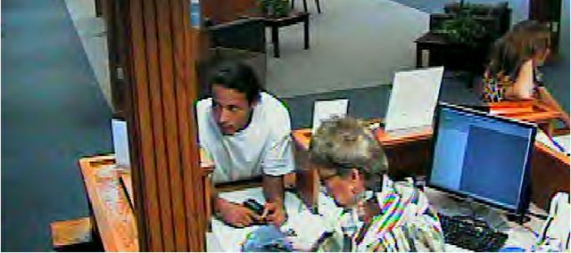 An unidentified man threatens a teller at the KU Credit Union, 3400 W. 6th Street, Monday afternoon. The suspect demanded money and then pulled cash out of the teller's drawer when he became impatient, police said.