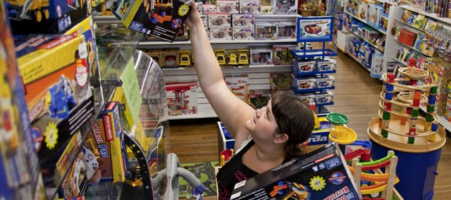 Store manager Rachel Ybarra pulls sale items from the shelves of The Toy Store, 936 Massachusetts, as she and other staff members work Tuesday afternoon to get organized for the sidewalk sale Thursday, July 15, 2010 in downtown Lawrence. Many local retailers devoted time throughout the early part of the week marking down prices for the sale which begins about 6 a.m. Thursday.