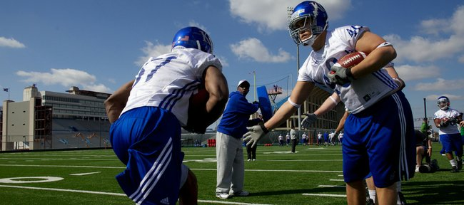 Kansas University running-backs coach Reggie Mitchell, center, leads a spring drill in this March 28 file photo at the KU practice fields. If a proposed NCAA rule change on when teams can offer scholarships is adopted, Mitchell said it would equalize recruiting battles around the country.