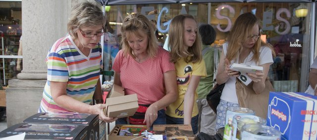 Demonstrating how the family that shops together stays together, sisters Joyce Burns, Carol Supancic, Carol's daughter Timber, 15, all of Lawrence, and Joyce and Carol's sister, Lisa Thompson, Houston, browse a table of items outside Hobbs Inc. during today's Downtown Lawrence Sidewalk Sale.