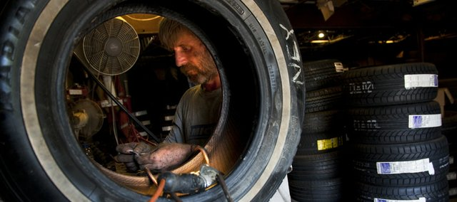 Kevin Parris, Oskaloosa, works to repair a tire in the back shop of D&D Tire Inc., 1000 Vt., on Tuesday. Phil Dwyer, owner of D&D, explained that blowouts occur in the summer because in hot temperatures, a tire cannot dissipate heat fast enough, which can cause the tire to wear much faster than in cooler temperatures.