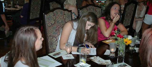 "Rachel Elise fills out paperwork during casting calls for ""The Bachelor"" and ""The Bachelorette."" Auditions for the reality show were Wednesday night at Renee Kelly's in Shawnee."