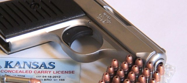 File photo of gun, bullets and Kansas concealed carry permit.
