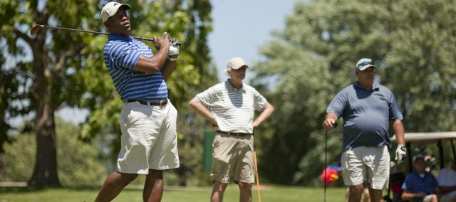 Kansas University football coach Turner Gill watches his drive from the first hole during Mario Chalmers' National Championship Golf Classic on Friday at Alvamar.