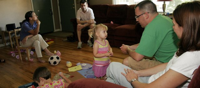 Landry Koester asks coloring advice from her father, Corey Koester. At right is her mother, Kari Koester, and sitting in the background are Rebecca and Eric Henry. In the foreground is the Henrys' daughter, Helen. The two families often share dinner and playdates, with only half a block separating their homes.