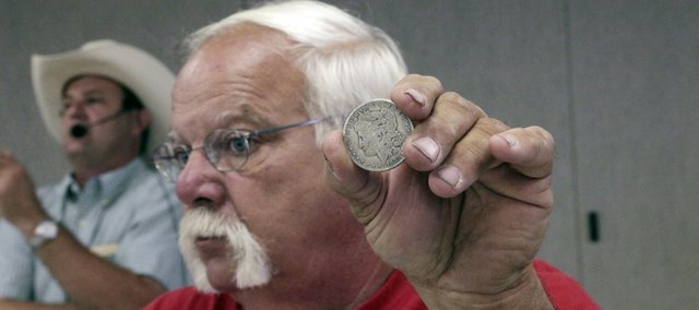Working the crowd with a Morgan silver dollar in his hand, Richard Anderson, of Baldwin City, helped auctioneer Mark Elston, left, go through a sale of old coins at the Douglas County Fairgrounds.