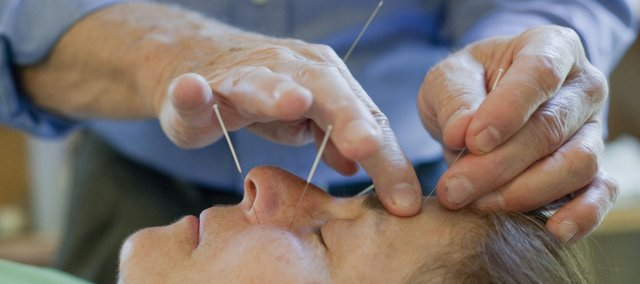 Jeff Nichols, M.D., provides an acupuncture procedure for sinus relief to Deb Carter.