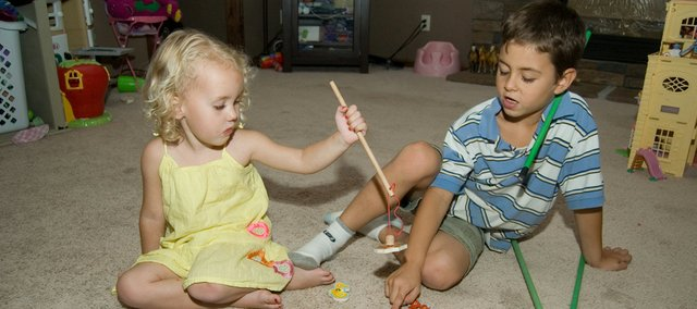 Brooklyn Sickman, 3, plays a puzzle game with her brother Nicholas Hernandez, 7. Brooklyn was severely injured last fall when an unhinged barn gate fell on her. Her doctors say she is making a remarkable recovery.