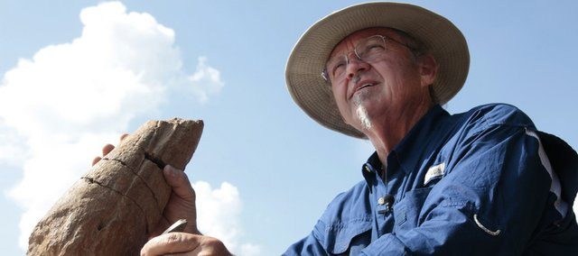 Alan Detrich holds a horn of a triceratops, left, and tooth of a tyrannosaurus rex. Detrich recently found more than half of a triceratops in Montana and will clean and assemble the bones. He also wants the state of Kansas to choose an official fossil.