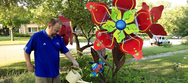 "Keeping things green: Clint Wedel, who lives at 700 Ohio waters his plants as colorful metal flowers help adorn the yard and never get brown.  ""Some people just stop and say it makes their day,"" Wedel said as he kept watering."