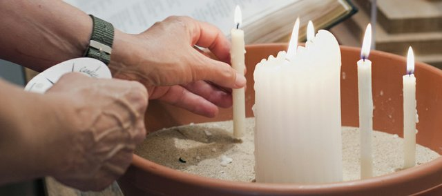 A worshipper adds to the collection of candles during the monthly Taize service held at Plymouth Congregational Church, 925 Vt.