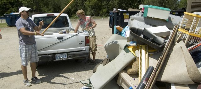 Nick Hoegler and David Howe II, both of Tonganoxie, throw items on to a pile of unwanted items Saturday during Tonganoxie's citywide cleanup.