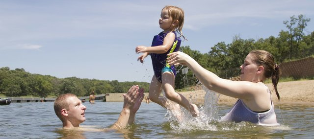 Ottawa residents Josh Sams, left, and Lexie Sams, right, stayed cool as they tossed their daughter, Abby, 2, between one another in this file photo at Lone Star Lake. The lake, about 12 miles southwest of Lawrence, is owned by the county. The Public Works Department, after a review following two recent drowning deaths, doesn't plan to seek any major changes to lake regulations.