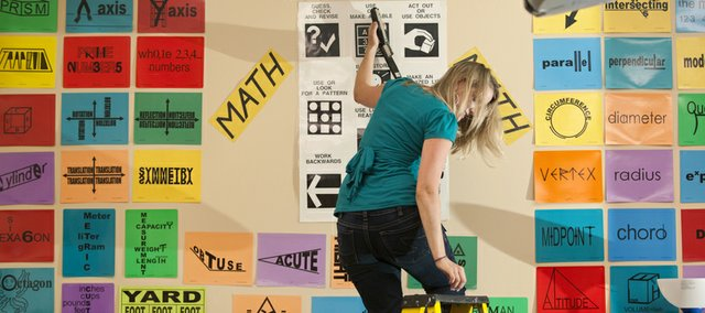 Fifth-grade teacher Monica Dutcher searches for a letter as she tidies up a wall featuring various clues and strategies for problem solving in preparation for the first day of school, Tuesday, Aug. 3, 2010 at Pinckney Elementary. Dutcher, who says she will be primarily teaching math to fifth and sixth graders, is one of several new teachers to the district.