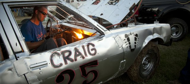 Chris Craig, Lawrence, uses a blow torch between rounds to cut a hole for his shifter in preparation for a consolation round during the Douglas County Fair Demolition Derby. After initial rounds at Friday evening's event, derby competitors like Craig could be found hurriedly fixing their cars with sledgehammers, wrenches and even intense heat.