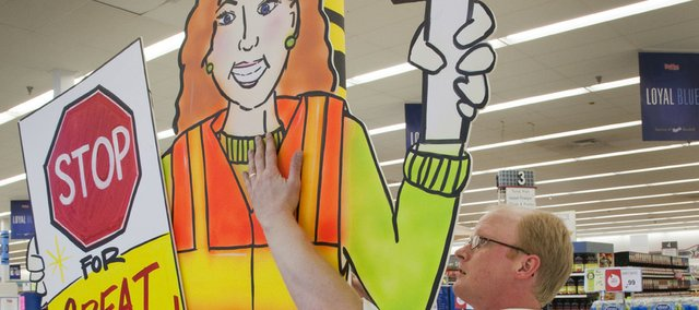 Steve Merz, assistant manager at Hy-Vee, 4000 W. Sixth St., puts up a school supply display at the store. Lawrence public school classes resume this week.