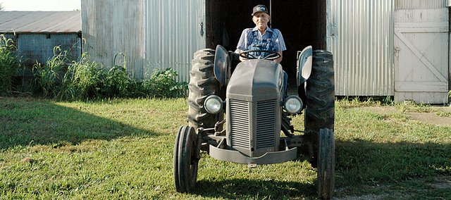 Max Moore sits on his 1950 Ferguson tractor after pulling it out of one of his barns on his farm north and west of Baldwin City Tuesday morning. Moore was undefeated on his favored Ferguson during the years he entered the Vinland Fair tractor pull. The 92-year-old will be there with it Friday to be recognized.