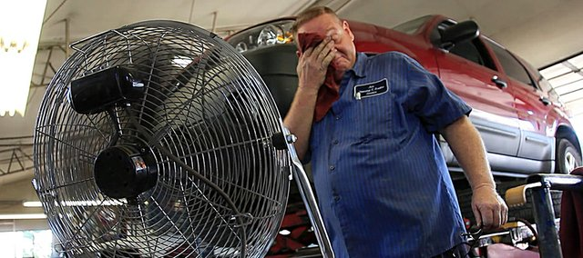 Danny Easum wipes his brow in front of a fan at Ace Brake and Steering, 541 Minnesota, on Wednesday, August 11, 2010.