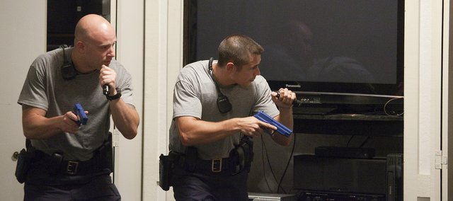 Recruits with the Lawrence Police Department work on building search scenarios Thursday at the Knights of Columbus building at 2206 E. 23rd St. Recruits Ken Rodgers, left, and Matt Hogan slowly approach doorways inside the building in a mock burglary alarm training.