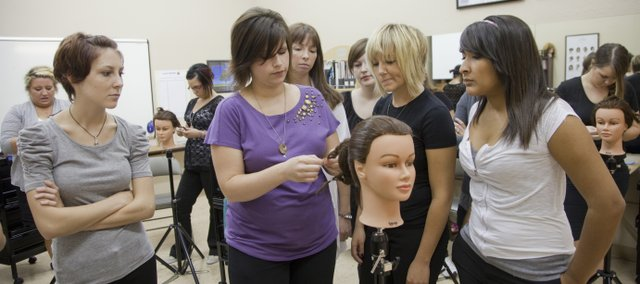 Lauren Willis, left of center, an instructor at Z's Cosmetology Academy, teaches a basics course at the site, 2429 Iowa. Enrollment is up at vocational schools in the area as students look for alternate career paths in a down economy.